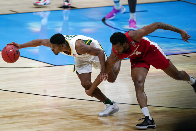 Baylor guard Jared Butler, left, runs down a loose ball ahead of Houston forward Justin Gorham (4) during the first half of a men's Final Four NCAA college basketball tournament semifinal game, Saturday, April 3, 2021, at Lucas Oil Stadium in Indianapolis. (AP Photo/Michael Conroy)