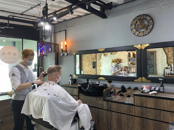 A barber and a male customer wear face masks during a haircut at a barber shop on Tuesday, May 12, 2020 in Singapore. Singapore has allowed selected businesses such as traditional Chinese medicine medical halls, home-based establishments, food manufacturing, selected food retail outlets, laundry services, traditional barbers and pet supplies to reopen May 12 in a cautious rollback of a two-month partial lockdown to curb the spread of COVID-19 infections in the city-state. (AP Photo/Royston Chan)