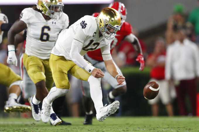 Notre Dame quarterback Ian Book (12) works to recover a missed snap against Georgia during the first half of an NCAA college football game, Saturday, Sept. 21, 2019, in Athens, Ga. (AP Photo/John Bazemore)