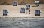 A man take a shower in front of empty beach chairs at the Strandbad Wannsee a public swimming area at the Wannensee lake in Berlin, Germany, May 25, 2020. Berlin's open-air swimming pools reopen after the lockdown because of the coronavirus crisis. In future, 400 guests will be allowed to enter the lido in the morning and in the afternoon again, subject to safety distances and prior notification. (Michael Kappeler/dpa via AP)