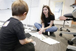 In this Oct. 27, 2019 photo, Univ. of Delaware senior Caitlin Berger wants to see what fabric swatches 7-year old Calvin  likes  at the Innovation Health and Design Lab at the University of Delaware in Newark, Del. Calvin was participating in the Down Syndrome Research Party. (Elizabeth Robertson/The Philadelphia Inquirer via AP)