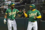 Oakland Athletics' Starling Marte, left, and Elvis Andrus celebrate after they scored on Matt Olson's three-run double during the second inning of a baseball game against the Texas Rangers in Oakland, Calif., Friday, Sept. 10, 2021. (AP Photo/Jeff Chiu)