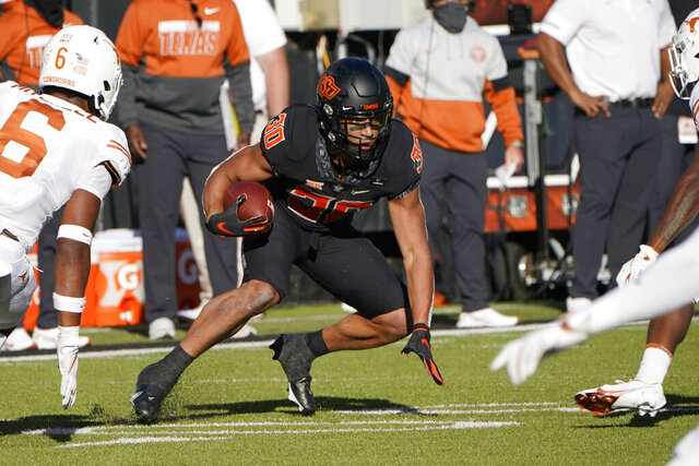 Oklahoma State running back Chuba Hubbard (30) carries past Texas linebacker Juwan Mitchell (6) during the first half of an NCAA college football game in Stillwater, Okla., Saturday, Oct. 31, 2020. (AP Photo/Sue Ogrocki)