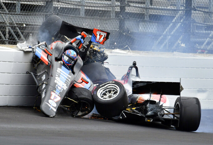 The car driven by Chris Windom (17) rides on the top of the car driven by David Malukas after a crash in the fourth turn during the running of the Indy Lights Freedom 100 IndyCar auto race at Indianapolis Motor Speedway, Friday, May 24, 2019, in Indianapolis. (AP Photo/Larry Drake)