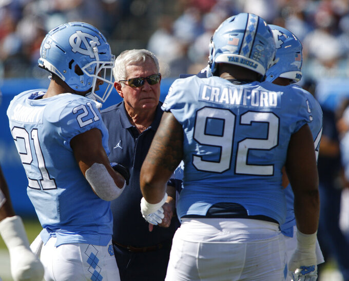 """FILE - North Carolina head coach Mack Brown talks to linebacker Chazz Surratt (21) and defensive lineman Aaron Crawford (92) as they play South Carolina in the first half of an NCAA college football game in Charlotte, N.C., Saturday, Aug. 31, 2019. With ACC football teams set to begin play this week, some league schools have tried to reduce campus population density through remote instruction to minimize interactions in classrooms and elsewhere. """"I think it was outside the classroom where students had gotten in trouble,"""" Tar Heels coach Mack Brown said. (AP Photo/Nell Redmond, File)"""