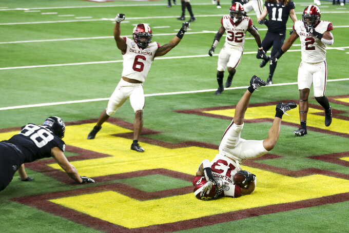 Oklahoma defensive back Tre Norwood (13) intercepts a pass in the end zone intended for Iowa State tight end Charlie Kolar (88) during the first half of the the Big 12 Conference championship NCAA college football game, Saturday, Dec. 19, 2020, in Arlington, Texas. (Ian Maule/Tulsa World via AP)