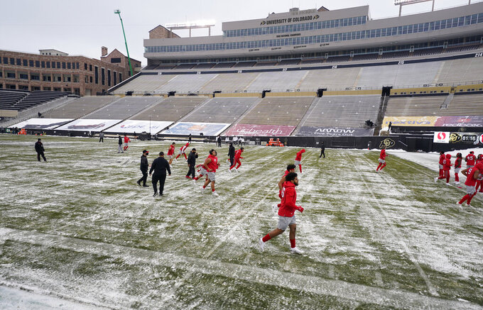 Utah players warm up in sub-freezing temperatures and light snow before the first half of an NCAA college football game against Colorado Saturday, Dec. 12, 2020, in Boulder, Colo. (AP Photo/David Zalubowski)