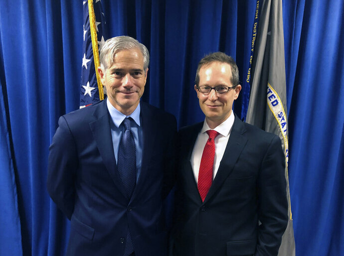In this Tuesday, Oct. 29, 2018, photo David DeVillers, left, a veteran prosecutor confirmed this week by the U.S. Senate to become U.S. Attorney for southern Ohio, stands with current U.S. Attorney Benjamin C. Glassman in the federal prosecutor's offices in Cincinnati. David DeVillers has been formally sworn into office, Friday, Jan. 10, 2020. (AP Photo/Dan Sewell)