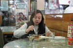 Customer has lunch with a transparent plastic panel setup on the table to isolate her from others in hopes of stopping the spread of the coronavirus in a Hong Kong, Wednesday, Feb. 12, 2020. China's ruling Communist Party needs to make a politically fraught decision: Admit a viral outbreak isn't under control and cancel this year's highest-profile official event. Or bring 3,000 legislators to Beijing next month and risk fueling public anger at the government's handling of the disease. (AP Photo/Kin Cheung)