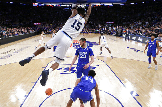 Villanova forward Saddiq Bey (15) hangs from the rim after dunking on Seton Hall guard Jared Rhoden (14) and forward Sandro Mamukelashvili (23) during the first half of an NCAA college basketball game in the championship of the Big East Conference tournament, Saturday, March 16, 2019, in New York.  Villanova won 74-72. (AP Photo/Julio Cortez)