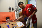 Minnesota Twins starting pitcher Jose Berrios shakes the hand of 7-year-old Lucas Suarez, during a visit by a group of Berrios' teammates at the San Jorge Children's Hospital in San Juan, Puerto Rico, Monday, April 16, 2018. Next Tuesday and Wednesday, the Cleveland Indians and the Minnesota Twins will meet in a two-game series at Hiram Bithorn Stadium in San Juan. (AP Photo/Carlos Giusti)