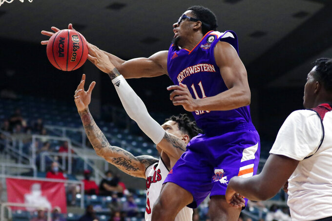 Northwestern State forward Jamaure Gregg (11) has his shot attempt knocked away by Nicholls State forward Najee Garvin, left, during the second half of an NCAA college basketball game in the Southland Conference semifinals Friday, March 12, 2021, in Katy, Texas. (AP Photo/Michael Wyke)