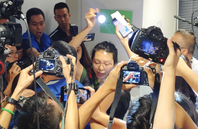 An unidentified alleged reporter, center, raises a flashlight to read a statement during a police news conference in Hong Kong, Monday, Oct. 28, 2019. The unidentified alleged reporter has disrupted the news conference to protest what she calls the escalating violence by officers against journalists covering the city's pro-democracy protests. (AP Photo/Kelvin Chan)
