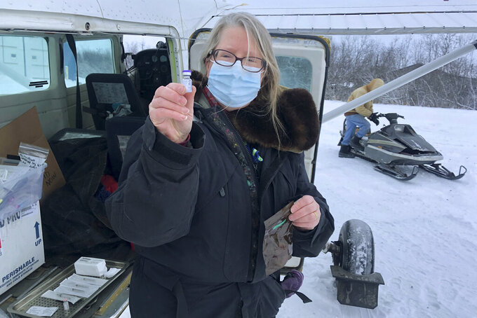 This December 2020 photo provided by Yukon Kuskokwim Health Corporation, Village Service Chief Dr. Elizabeth Roll holds a COVID-19 vaccine in Napakiak, Alaska. Getting the vaccine to the world's farthest corners means delivering it by boat to Maine's islands, traveling by snowmobile to villages in Alaska and navigating complex waterways in Brazil's Amazon. (Yukon Kuskokwim Health Corporation via AP)