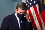 Gov. Roy Cooper prepares to take off his mask before speaking during a briefing at the Emergency Operations Center in Raleigh, N.C., Thursday, July 9, 2020. (Ethan Hyman/The News & Observer via AP)