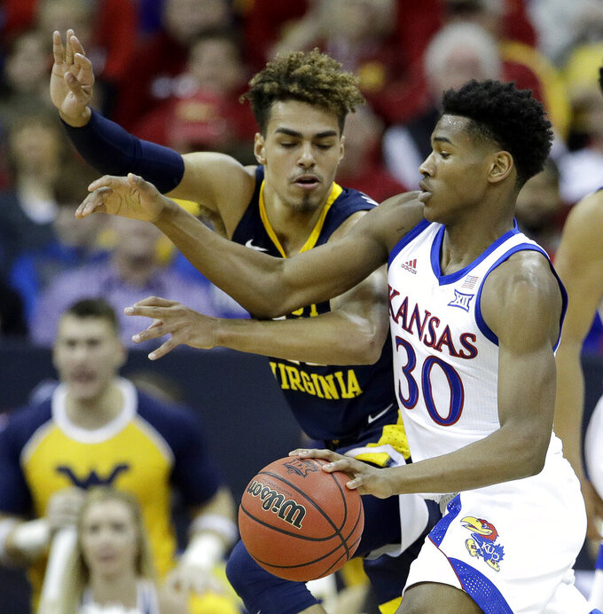 Kansas' Ochai Agbaji (30) is pressured by West Virginia's Emmitt Matthews Jr. during the first half of an NCAA college basketball game in the Big 12 men's tournament Friday, March 15, 2019, in Kansas City, Mo. (AP Photo/Charlie Riedel)