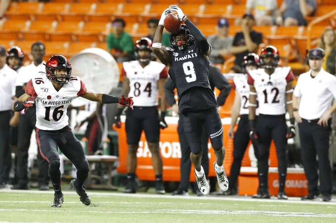 Hawaii wide receiver JoJo Ward catches the ball next to San Diego State cornerback Luq Barcoo (16) during the first half of an NCAA college football game Saturday, Nov. 23, 2019, in Honolulu. (AP Photo/Marco Garcia)