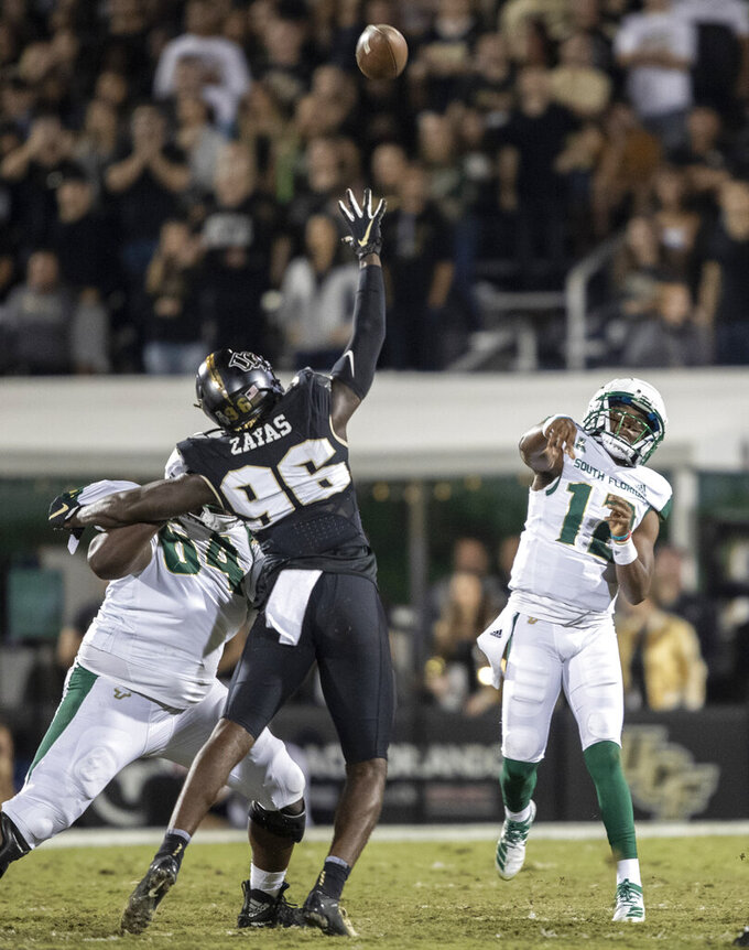 South Florida quarterback Jordan McCloud (12) launches a long pass over South Florida defensive lineman Stephon Zayas (96) during the first half of an NCAA college football game Friday, Nov. 29, 2019, in Orlando, Fla. (AP Photo/Willie J. Allen Jr.)