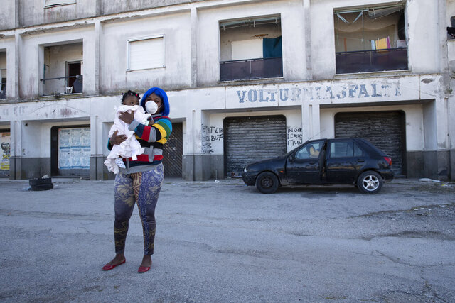 "FILE -- In this photo taken on Monday, April 27, 2020, a woman wearing a sanitary mask to protect against COVID-19 holds her daughter as she walks past a building in Castel Volturno, near Naples, Southern Italy. They are known as ""the invisibles,"" the undocumented African migrants who, even before the coronavirus outbreak plunged Italy into crisis, barely scraped by as day laborers, prostitutes and seasonal farm hands. Pope Francis is calling for migrant farm workers to be treated with dignity, issuing an appeal as Italy weighs whether to legalize undocumented agricultural workers amid a shortage of seasonal farm labor due to the coronavirus emergency. (AP Photo/Alessandra Tarantino)"