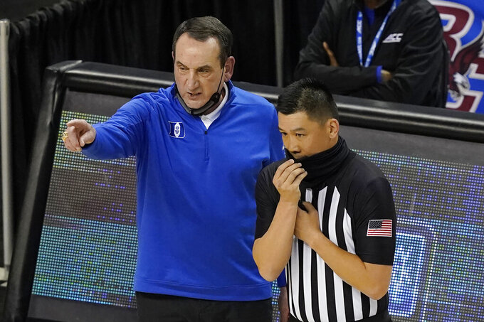 Duke head coach Mike Krzyzewski, left, talks with a ref during the first half of an NCAA college basketball game in the first round of the Atlantic Coast Conference tournament in Greensboro, N.C., Tuesday, March 9, 2021. (AP Photo/Gerry Broome)