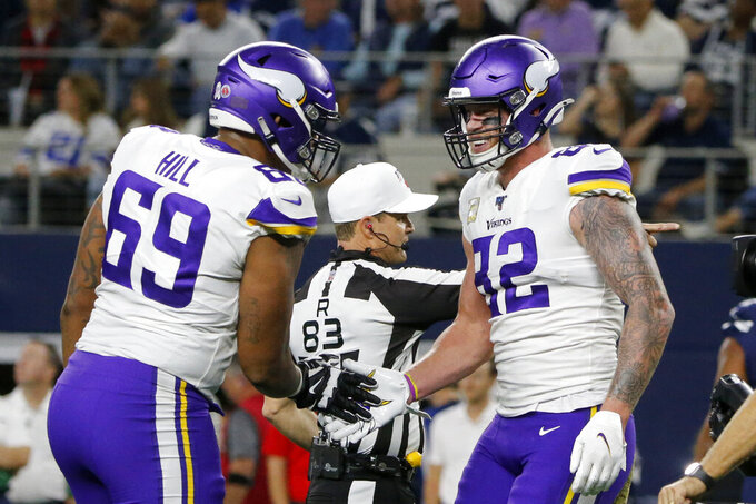 Minnesota Vikings offensive tackle Rashod Hill (69) and tight end Kyle Rudolph (82) celebrate a touchdown catch by Rudolph during the first half of the team's NFL football game against the Dallas Cowboys in Arlington, Texas, Sunday, Nov. 10, 2019. (AP Photo/Michael Ainsworth)