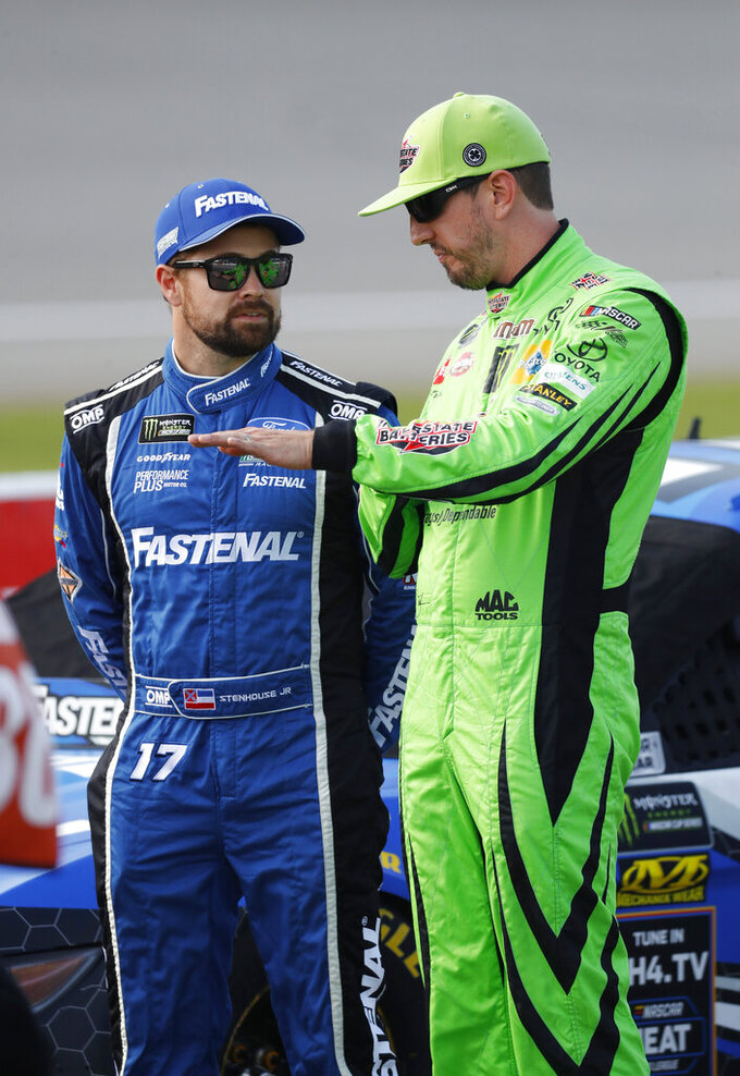 Ricky Stenhouse Jr., left, listens to Kyle Busch during qualifying for the NASCAR Cup Series auto race at Michigan International Speedway in Brooklyn, Mich., Friday, Aug. 9, 2019. (AP Photo/Paul Sancya)