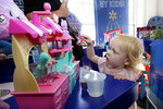 """In this Aug. 30, 2018, photo 20-month-old Eva plays with Num Nom Silly Shakers Maker toy at the Walmart Toy Shop event in New York. Walmart says 30 percent of its holiday toy assortment will be new. It will also offer 40 percent more toys on Walmart.com from a year ago. In November and December, the company's toy area will be rebranded as """"America's Best Toy Shop."""" (AP Photo/Richard Drew)"""