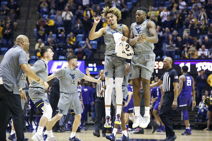 West Virginia forwards Emmitt Matthews Jr. (11) and Oscar Tshiebwe (34) celebrate after a score during the first half of the team's NCAA college basketball game against TCU on Tuesday, Jan. 14, 2020, in Morgantown, W.Va. (AP Photo/Kathleen Batten)