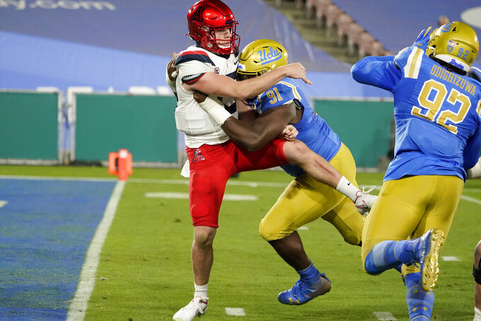 Arizona quarterback Will Plummer, left, is hit, just after a throw, by UCLA defensive lineman Otito Ogbonnia (91) during the first half of an NCAA college football game Saturday, Nov. 28, 2020, in Pasadena, Calif. (AP Photo/Marcio Jose Sanchez)