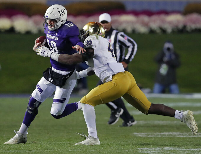 Northwestern's Clayton Thorson, left, tries to break a tackle by Notre Dame's Te'von Coney during the second half of an NCAA college football game Saturday, Nov. 3, 2018, in Evanston, Ill. (AP Photo/Jim Young)