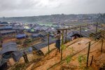 -FILE- In this Wednesday, Sept. 20, 2017, file photo A Rohingya Muslim man, who crossed over from Myanmar into Bangladesh, builds a shelter for his family in Taiy Khali refugee camp, Bangladesh. Gambia has filed a case at the United Nations' highest court in The Hague, Netherlands, Monday, Nov. 11, 2019, accusing Myanmar of genocide in its campaign against the Rohingya Muslim minority. A statement released Monday by lawyers for Gambia says the case also asks the International Court of Justice to order measures