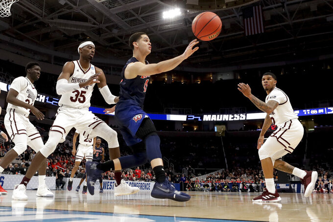 Liberty guard Georgie Pacheco-Ortiz passes the ball between Mississippi State guard Lamar Peters, right, and forward Aric Holman during the first half of a first-round game in the NCAA men's college basketball tournament Friday, March 22, 2019, in San Jose, Calif. (AP Photo/Jeff Chiu)