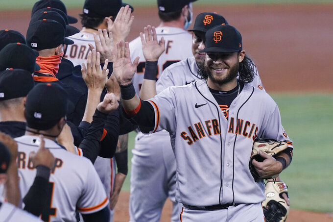 San Francisco Giants shortstop Brandon Crawford celebrates with the team after defeating the Miami Marlins 1-0, at a baseball game, Sunday, April 18, 2021, in Miami. (AP Photo/Marta Lavandier)