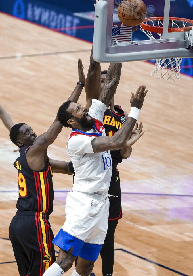 New Orleans Pelicans forward James Johnson (16) shoots over Atlanta Hawks forward Tony Snell (19) and forward Onyeka Okongwu (17) in the third quarter of an NBA basketball game in New Orleans, Friday, April 2, 2021. (AP Photo/Derick Hingle)