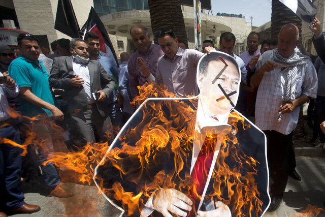 Palestinians burn a cutout of the U.S. Secretary of State Mike Pompeo, during a protest against his visit to Israel and U.S. President Donald Trump's Mideast initiative, in the West Bank city of Nablus, Thursday, May 23, 2020.(AP Photo/Majdi Mohammed)