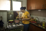 Fatma Youssef, a volunteer part of an initiative that sends meals to quarantined coronavirus patients, cooks a meal for a family, in her apartment, in Cairo, Egypt, Saturday, July 11, 2020. She and other volunteers in Egypt hope the meals will help nurse quarantined coronavirus patients back to health and provide them with some respite. In different neighborhoods in Cairo and some other cities they've enlisted people to cook, donate food or make contactless deliveries to patients' homes. (AP Photo/Nariman El-Mofty)