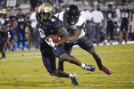 Central Florida wide receiver Marlon Williams (6) gains yardage in front of Cincinnati cornerback Arquon Bush after a reception during the second half of an NCAA college football game, Saturday, Nov. 21, 2020, in Orlando, Fla. (AP Photo/John Raoux)
