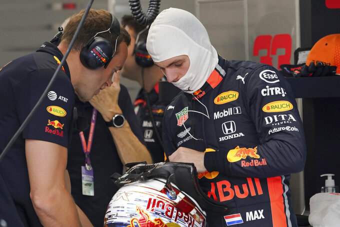 Red Bull driver Max Verstappen of the Netherlands chats with his crew member during the first practice session at the Marina Bay City Circuit ahead of the Singapore Formula One Grand Prix in Singapore, Friday, Sept. 20, 2019. (AP Photo/Vincent Thian)