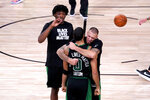 Boston Celtics' Jayson Tatum (0) is hugged by Daniel Theis as Robert Williams III, left, looks on while celebrating a win over the Toronto Raptors during an NBA conference semifinal playoff basketball game Friday, Sept. 11, 2020, in Lake Buena Vista, Fla. The Celtics won 92-87. (AP Photo/Mark J. Terrill)
