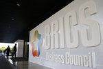 People walk past the BRICS Business Council sign prior the 11th edition of the BRICS Summit, in Brasilia, Brazil, Tuesday, Nov. 12, 2019. The BRICS Summit gathers the group of countries formed by Brazil, Russia, India, China and South Africa, which will take place in the 13th and 14th of this month. (AP Photo/Eraldo Peres)