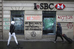 People walk past a vandalized bank after Thursday's violence, Friday, Dec. 6, 2019 in Paris. Frustrated travelers are meeting transportation chaos around France for a second day, as unions dig in for what they hope is a protracted strike against government plans to redesign the national retirement system. (AP Photo/Rafael Yaghobzadeh)