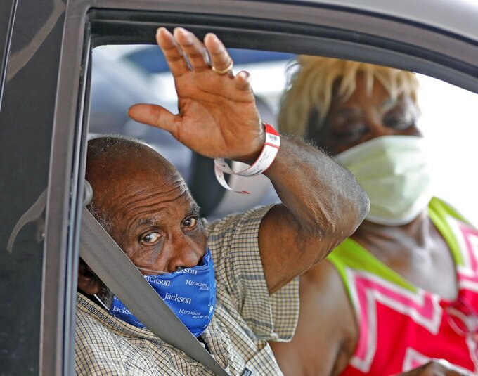 James Gardner, 77, goes home after battling COVID-19 for a month at Jackson South Medical Center,  Thursday, Aug. 27, 2020 in Miami. (Al DIaz/Miami Herald via AP)