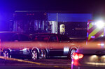 In this Thursday, Dec. 5, 2019, photo authorities investigate the scene of a shooting in Miramar, Fla. The FBI says several people, including a UPS driver, were killed after robbers stole the driver's truck and led police on a chase that ended in gunfire at a busy South Florida intersection during rush hour. (Taimy Alvarez/South Florida Sun-Sentinel via AP)