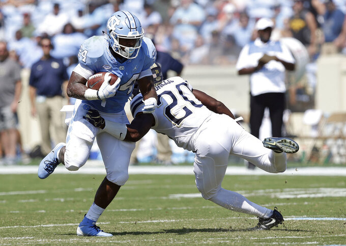 North Carolina's Antonio Williams (24) runs the ball while Pittsburgh's Dennis Briggs (20) tries to make the tackle during the first half of an NCAA college football game in Chapel Hill, N.C., Saturday, Sept. 22, 2018. (AP Photo/Gerry Broome)