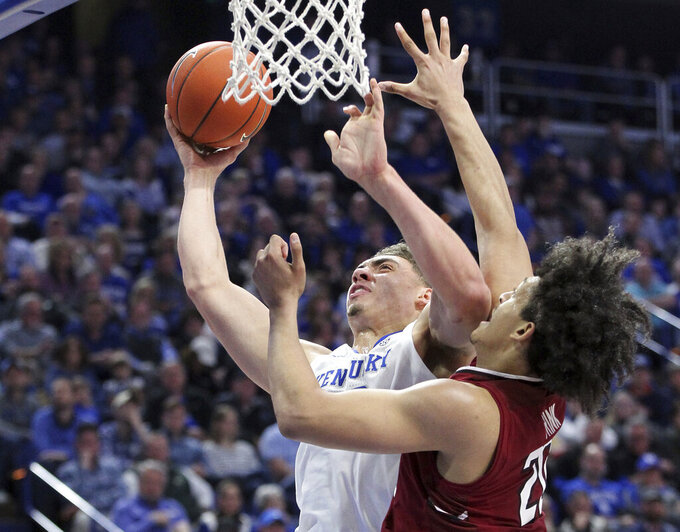 Kentucky's Reid Travis, left, shoots while defended by South Carolina's Alanzo Frink during the first half of an NCAA college basketball game in Lexington, Ky., Tuesday, Feb. 5, 2019. (AP Photo/James Crisp)