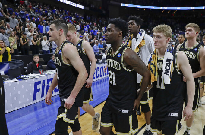 Wofford players including Fletcher Magee, left, Tray Hollowell (21), and Ryan Larson, front right, leave the court after losing to Kentucky of a second-round game in the NCAA men's college basketball tournament in Jacksonville, Fla., Saturday, March 23, 2019. (AP Photo/John Raoux)