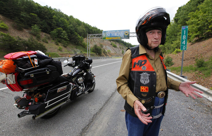 E. Bruce Heilman at age 87 stands by his Harley Davidson motorcycle near the Virginia-West Virginia border June 8, 2014. The former University of Richmond president and well-known veterans' advocate died Saturday Oct. 19, 2019 at age 93. (Bob Brown/Richmond Times-Dispatch via AP)