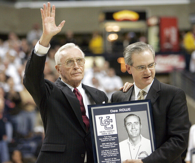 FILE - In this Feb. 5, 2007, file photo, former University of Connecticut head men's basketball coach Dee Rowe, left, waves to the crowd after he was presented with a plaque by UConn director of athletics Jeff Hathaway at a ceremony honoring former UConn basketball players and coaches at halftime of an NCAA college basketball game against Syracuse in Storrs, Conn. Rowe, who served for more than five decades as an ambassador for the school's athletic department and as a mentor for coaches including Jim Calhoun and Geno Auriemma, died on Sunday, Jan. 10, 2021.  He was 91. (AP Photo/Bob Child, File)