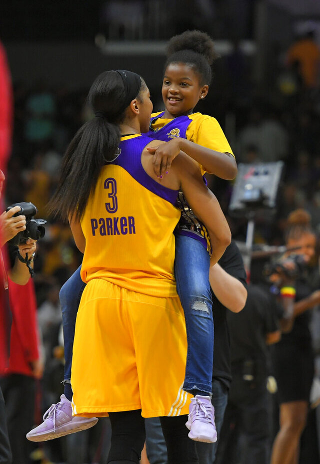"FILE- In this Sept. 29, 2017, file photo, Los Angeles Sparks forward Candace Parker holds her daughter Lailaa Nicole Williams after Game 3 of the WNBA basketball finals against the Minnesota Lynx in Los Angeles. The Sparks won 75-64. Parker and her 11-year-old daughter are braving the start of an unprecedented WNBA season together in Florida. The Los Angeles Sparks All-Star knows it's a calculated risk to stay in the coronavirus hot spot, where all 12 teams will play games in the WNBA ""bubble"" of Bradenton. (AP Photo/Mark J. Terrill, File)"