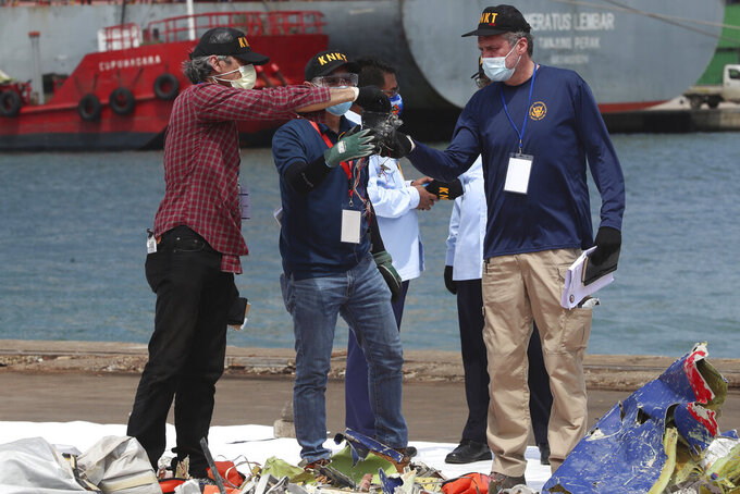 Members of the U.S. National Transportation Safety Board (NTSB) investigators team inspect debris found in the waters around the location where a Sriwijaya Air passenger jet crashed, at the search and rescue command center at Tanjung Priok Port in Jakarta, Indonesia, Saturday, Jan. 16, 2021. The NTSB joined the crash investigation with Indonesian National Transportation Safety Committee. (AP Photo/Achmad Ibrahim)